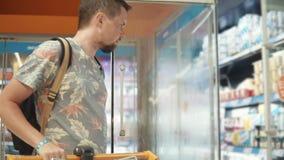 O homem é porta de abertura do refrigerador no supermercado e tomada do iogurte video estoque