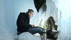 O homem é senta-se no Internet no portátil em uma caverna de gelo Em torno da gruta bonita misteriosa do gelo O usuário comunica- imagens de stock