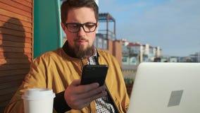 O homem é tela de vista do smartphone que senta-se fora, com portátil e café vídeos de arquivo