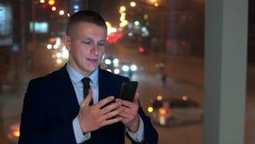 O homem é um homem de negócios, olhando o smartphone e irritado, tentando conter a raiva video estoque
