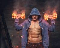 O homem abdominal em um hoodie azul guarda os pesos ardentes imagem de stock royalty free
