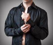 O homem abotoa a camisa preta da luva Imagens de Stock Royalty Free