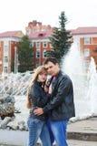 O homem abraça a mulher nos casacos de cabedal perto da fonte fotografia de stock royalty free