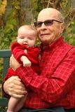 O homem abraça seu great-granddaughter enquanto sorriem Imagens de Stock Royalty Free