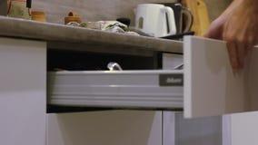 O homem abre a caixa extraível da cozinha com o sistema do impulso video estoque