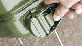 O homem abre a gasolina do gás ou o bidão do diesel com combustível filme