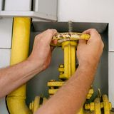 O homem abre ou fecha-se em uma válvula da tubulação de gás para controlar o enterin dos gáss fotos de stock