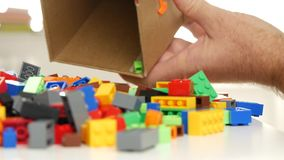 O homem abre uma caixa com os tijolos plásticos pequenos coloridos para Toy Constructions video estoque