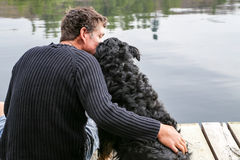 O homem aconchega-se o cão no lago Imagens de Stock