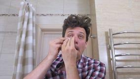 O homem acordado cansado com um bocejo da manutenção no banheiro, põe-se em ordem, cola remendos sob os olhos vídeos de arquivo