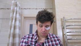 O homem acordado cansado com um bocejo da manutenção no banheiro, põe-se em ordem, cola remendos sob os olhos filme