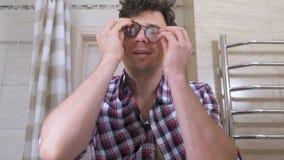 O homem acordado louco com uma manutenção põe sobre seus vidros no banheiro e põe-se em ordem vídeos de arquivo