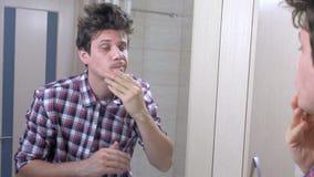 O homem acordado sonolento cansado com uma manutenção no banheiro, olha o espelho e põe-se em ordem video estoque