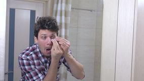 O homem acordado sonolento cansado com uma manutenção no banheiro, põe-se em ordem, cola remendos sob os olhos video estoque