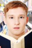 O homem adolescente novo está lendo um livro. imagem de stock royalty free