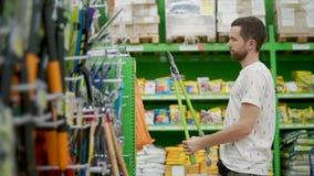 O homem adulto é de observação e de tentativa podando a tesoura em uma loja de ferragens filme