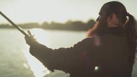 O homem adulto com barba longa está pescando guardando a vara de pesca O homem levanta e abaixa o gerencio Movimento lento video estoque