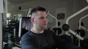 O homem adulto com excesso de peso executa a extensão do pé filme