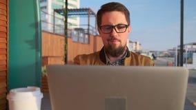 O homem adulto contente está olhando o filme no caderno, sentando-se no ar livre vídeos de arquivo