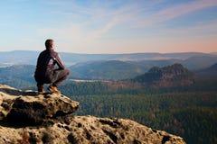 O homem adulto de escalada na parte superior da rocha com vista aérea bonita do vale enevoado profundo grita Imagem de Stock Royalty Free