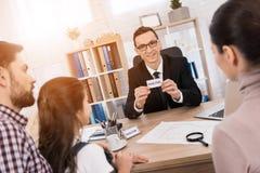 O homem adulto de sorriso mostra o cartão com inscrição pelo corretor de imóveis conceito de vendas dos bens imobiliários Casa pa fotos de stock royalty free