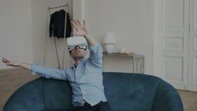 O homem adulto emocional está olhando o vídeo de 360 graus em casa, vestindo auriculares de VR Muito é surpreendido, olha ao redo filme