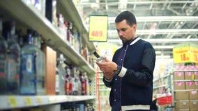 O homem adulto escolhe uma bebida alcoólica forte, os olhares da garrafa como a vodca vídeos de arquivo