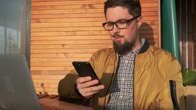 O homem adulto está conversando pelo telefone celular que senta-se na varanda no dia ensolarado vídeos de arquivo