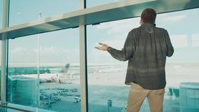 O homem adulto está falando pelo telefone celular no terminal do aeroporto, vista traseira vídeos de arquivo