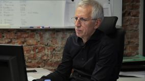 O homem adulto está trabalhando atentamente no escritório na frente do computador filme