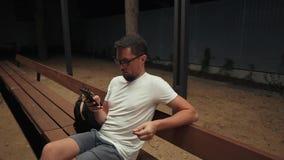 O homem adulto está vendo a notícia de redes sociais pelo telefone celular na noite no parque filme