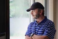 O homem adulto medita o futuro que olha para fora a chuva coberta Fotografia de Stock Royalty Free