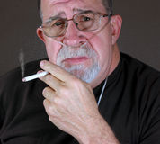O homem adulto no oxigênio fuma perigosamente um cigarro Foto de Stock Royalty Free