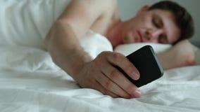 O homem adulto novo dorme, acorda e desabilita o telefone vídeos de arquivo