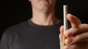 O homem adulto novo guarda um cigarro em uma mão e quebra-o então video estoque