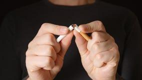 O homem adulto novo guarda um cigarro nas mãos e quebra-o vídeos de arquivo