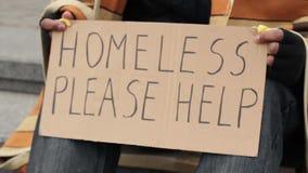 O homem adulto que guarda sem abrigo ajuda por favor a assinar, pobreza, vulnerabilidade social video estoque