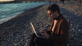 O homem adulto senta-se em uma praia de pedra durante o por do sol, pessoa contratado na programação video estoque