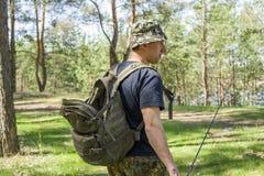 O homem adulto vai pescar com uma vara de pesca e uma trouxa foto de stock royalty free