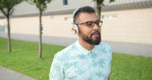 O homem africano considerável entusiasmado nos óculos de sol é de canto e de apreciação a música nos fones de ouvido durante sua  video estoque