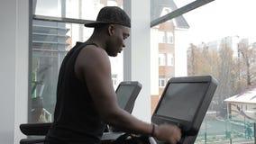 O homem africano está na escada rolante no clube desportivo filme