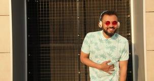 O homem africano feliz nos óculos de sol e nos fones de ouvido é rir exterior metragem 4k video estoque
