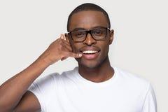 O homem africano nos mon?culos faz o gesto com m?o chama-me imagens de stock royalty free