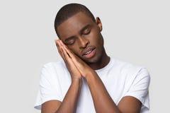 O homem africano p?s sua cabe?a em seus bra?os e sonos foto de stock