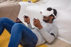 O homem africano veste óculos de proteção da realidade virtual, guarda controladores do jogo em casa fotos de stock