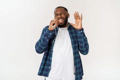 O homem afro-americano considerável na roupa ocasional está escutando a música usando um telefone e um sorriso espertos imagem de stock