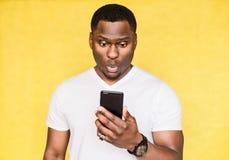 O homem afro-americano considerável perplexo e preocupado guarda o smartphone, olha fixamente com expressão surpreendida imagens de stock