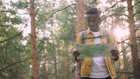 O homem afro-americano de sorriso está andando na floresta que olha o mapa que procura pelo destino desejado do turista que recom video estoque