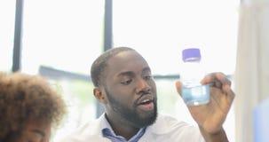 O homem afro-americano discute com os colegas de Team Liquid In Bottle Diverse dos cientistas que trabalham junto na experiência  vídeos de arquivo