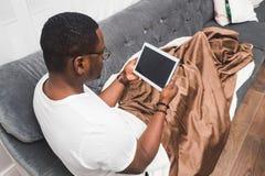 O homem afro-americano novo, coberto com uma cobertura, usa a tabuleta imagem de stock